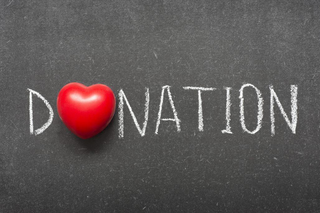 donation word handwritten on school blackboard with heart symbol instead of O